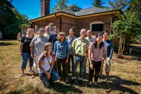 Architect Charlie Wenzlau and his team are among several firms contributing services to the Fort Ward Community Hall project. Pictured outside the historic Fort Ward bakery building are (front row, L-R) Ariel Jamison, Mary White Peters, Charlie Wenzlau and Jane Chung, all of Wenzlau Architects; (back row, L-R) Stephanie Appleberry of Friends of Fort Ward, Tina Gilbert of OTWB, Inc., David Harry of the Bainbridge Park District, Mike Gorham and Ross Grier of Wenzlau Architects, Doug Slingerland of the Park District, and Kee Song of the Wenzlau firm.