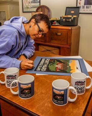 Alex Sanso signs a commemorative Fort Ward print