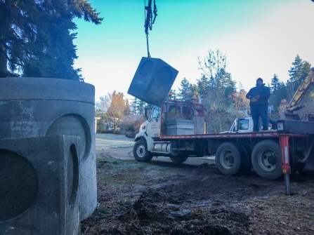 A concrete stormwater vault is lifted off the delivery truck