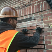 Eric from MRC plugs in the final brick in the north wall reconstruction